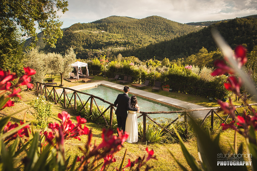 019-bride-groom-looking-tuscany-panorama-flowers-pool