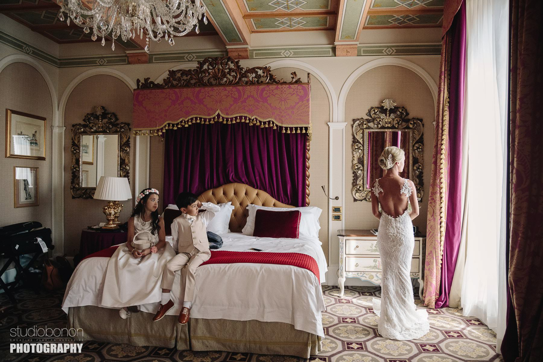 Elegant bride bride in her wedding gown at St. Regis luxury suite in Florence with flower girl and rig boy