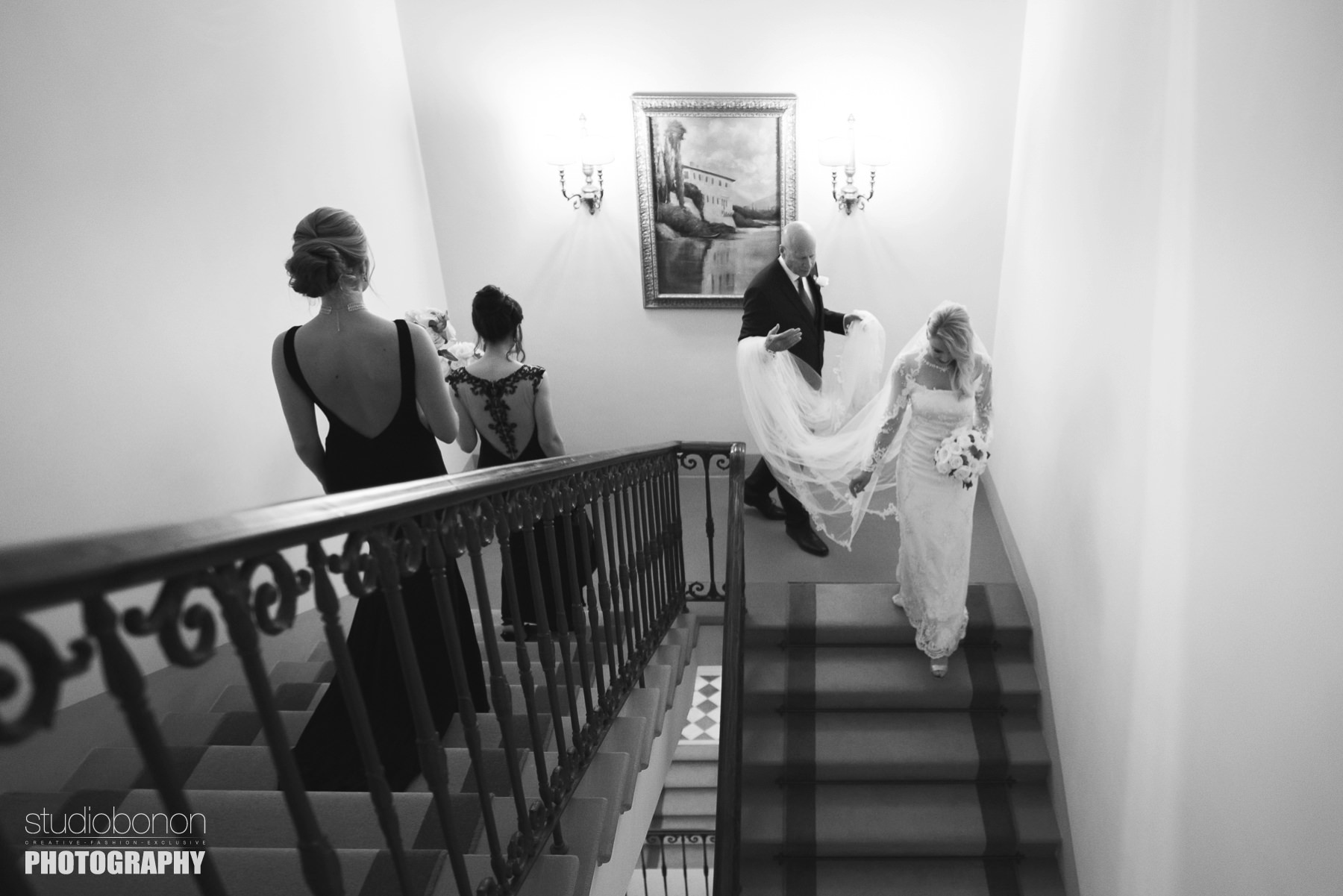 Bride Amy walks down hotel Four Seasons staircase with father and black dress elegant bridesmaids