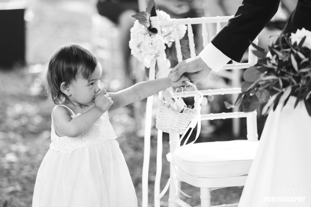 Lovely moment with flower girl during outdoor wedding ceremony. Destination wedding in Tuscany at Tenuta di Castelfalfi