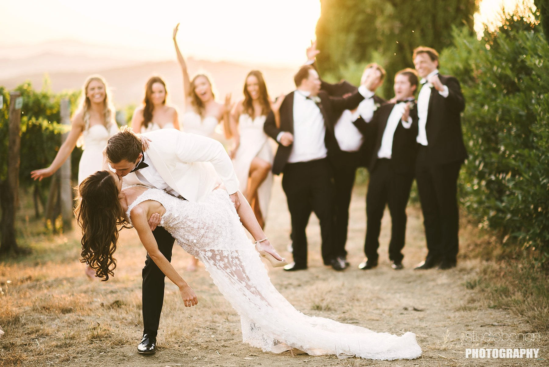 Tuscany countryside destination wedding in Panzano, Chianti. Bride and groom are sharing some love with the bridal party