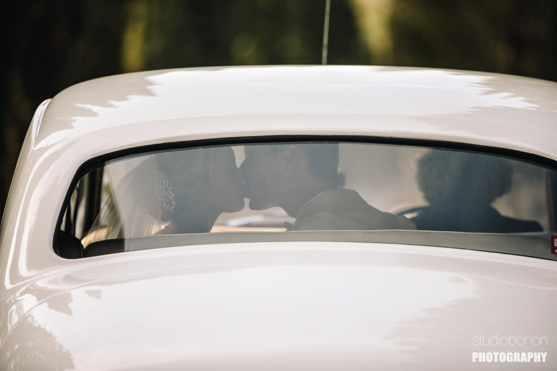 Bride and groom kiss into Rolls Royce at Vicigliata Castle into Florence countryside. Elegant destination luxury wedding