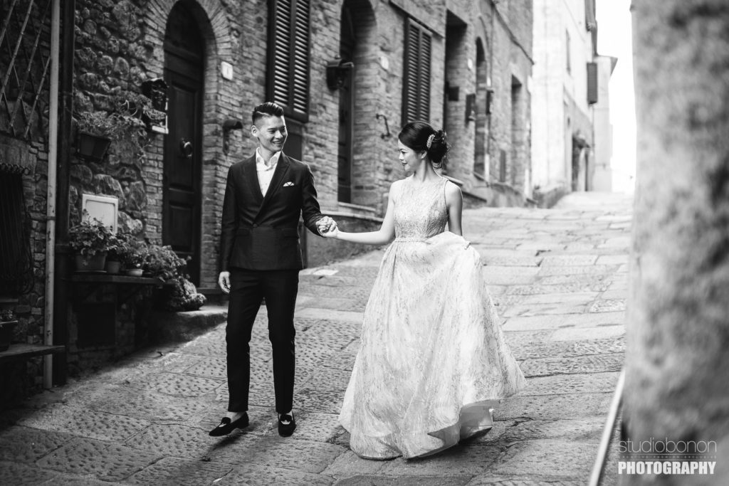 Bride and groom candid portrait in Tuscany countryside borgo near San Galgano