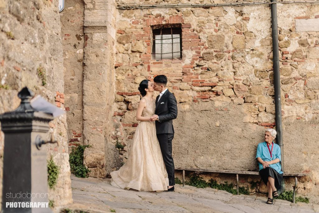 Bride and groom traditional Italian portrait in Tuscany countryside borgo near San Galgano