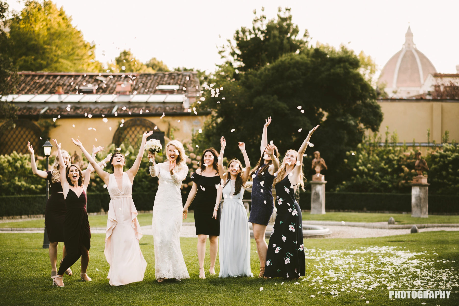 Excited bride with friends throw white petals at Hotel Four Seasons Florence. Destination Wedding in Florence