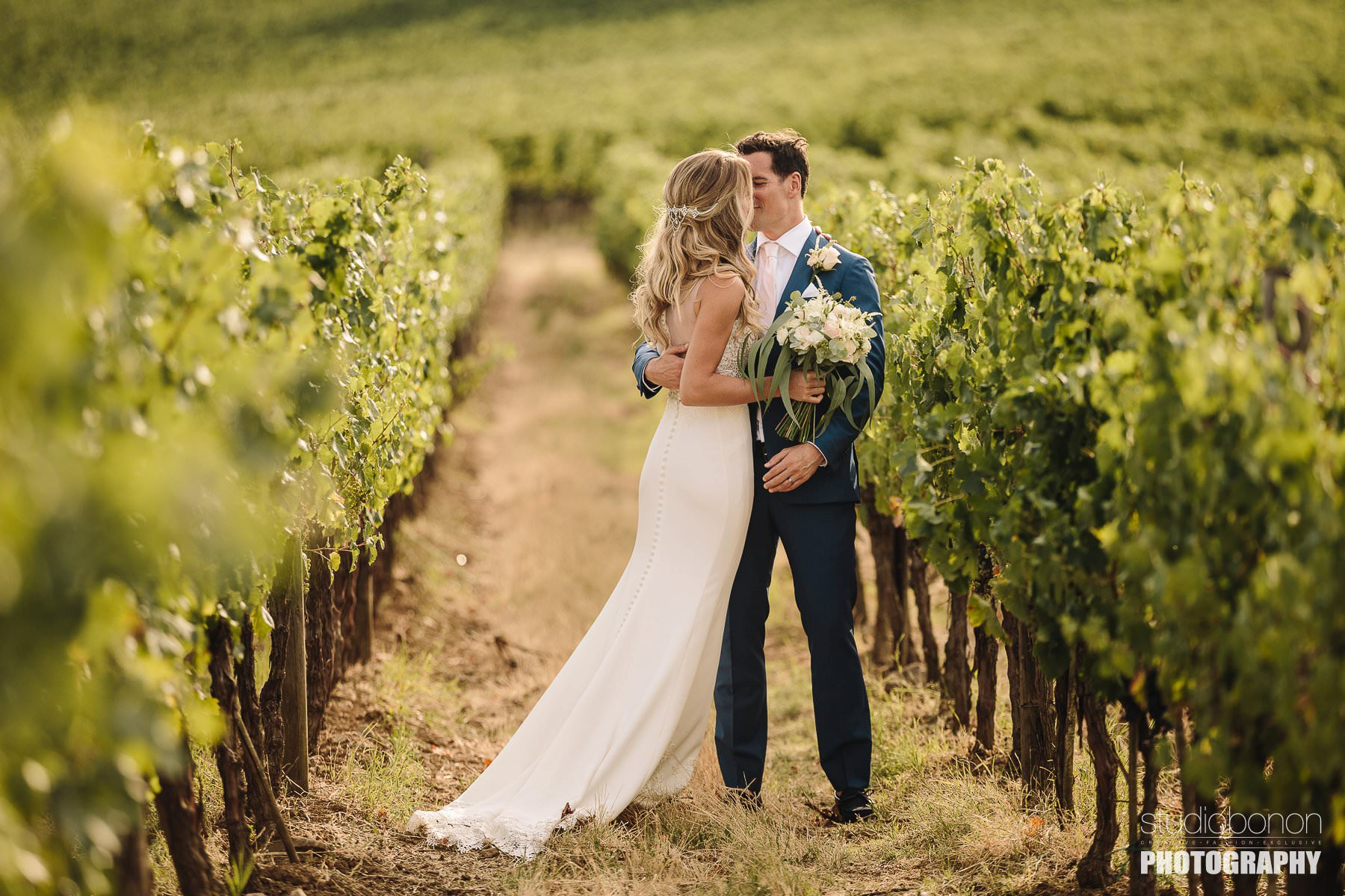Bride and groom wedding photo into the vineyard. Tuscany countryside destination wedding
