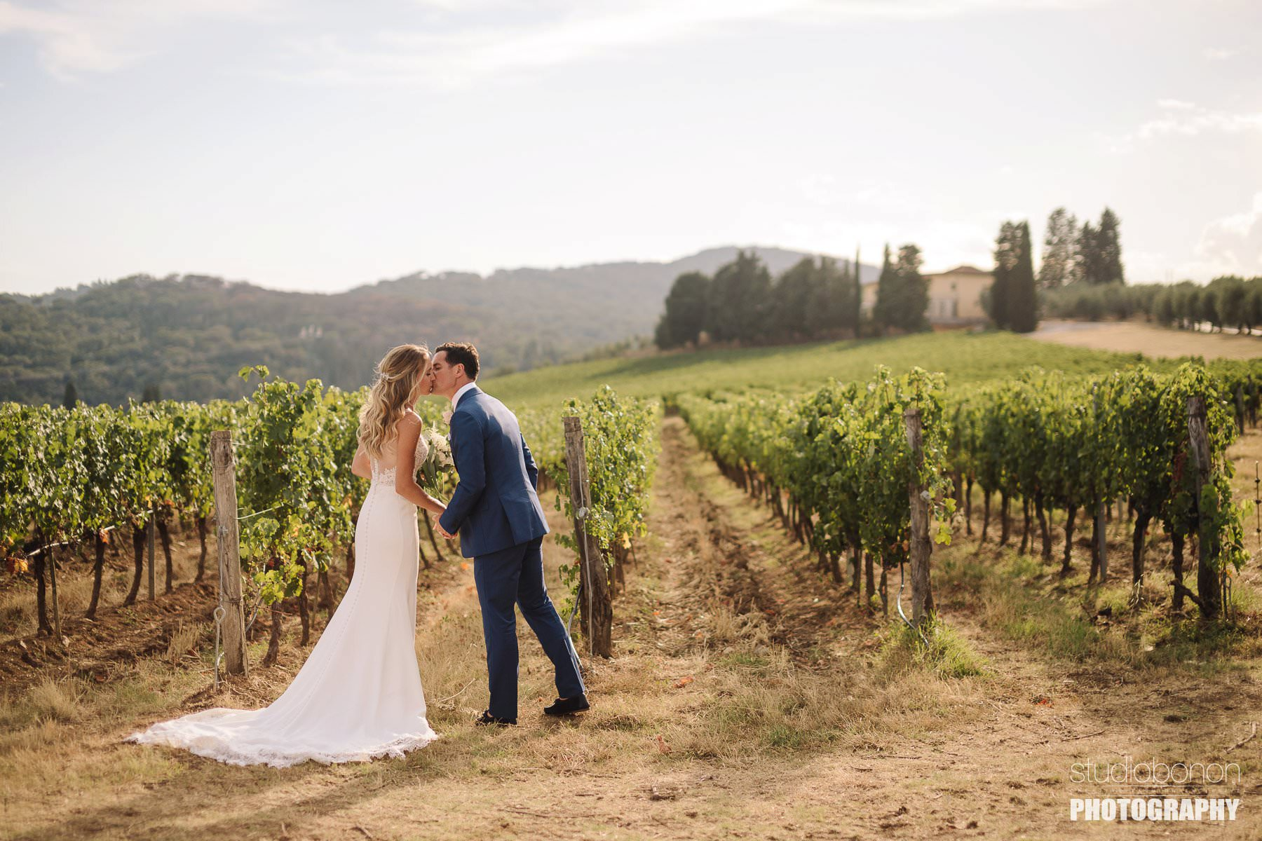 Bride and groom walk in a Tuscan vineyard into the countryside of Chianti